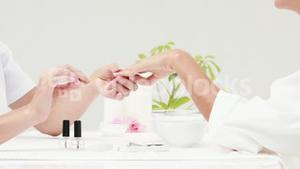Woman getting a manicure at nail salon