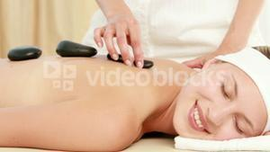 Smiling blonde getting hot stone massage
