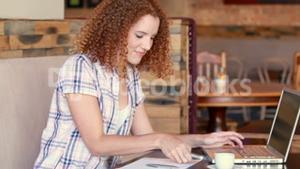 Pretty woman using her laptop computer and having phone call