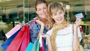Happy friend holding shopping bag and showing credit card