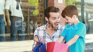 Father and son looking in shopping bag