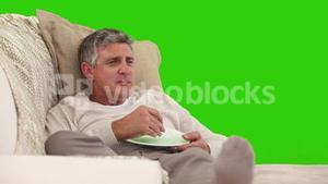 Elderly man eating in front of the tv