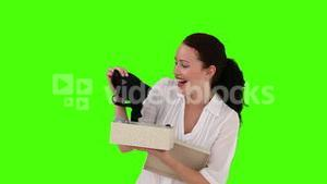 Darkhaired woman opening a present