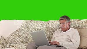Retired man using his computer in his living room