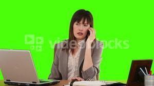 Businesswoman using a laptop and a phone to work