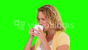 Curlyhaired woman drinking a cup of tea