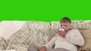 Retired man drinking a cup of tea on his sofa