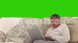 Retired man chatting on his computer in the living room