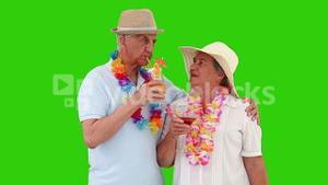 Mature couple sipping a cocktail on the beach