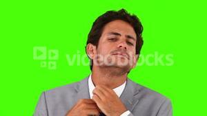 Young businessman putting on his tie
