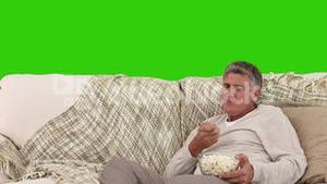 Middleage man eating popcorn while he is watching tv