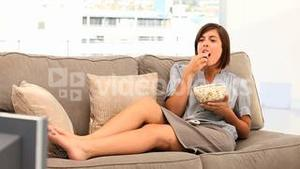 Casual brunette woman watching tv with popcorn