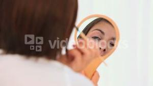 Brunette looking at herself on a mirror