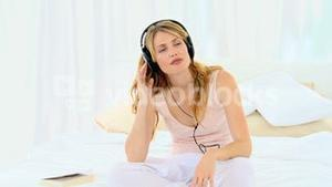 Casual blonde woman listening to music