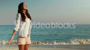 Happy woman with arms outstretched at the beach