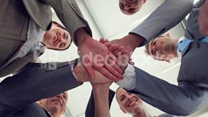 Business colleagues putting their hands together