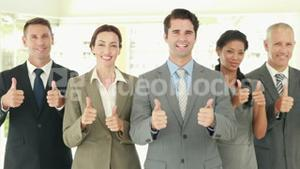 Smiling business people looking at camera gesturing thumbs up