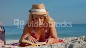 Pretty blonde woman lying on towel and reading book