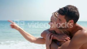 Happy cute couple hugging at the beach