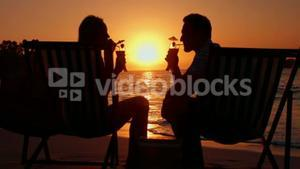 Couple drinking couple during the sunset on the beach
