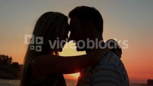 Cute couple hugging during the sunset on the beach