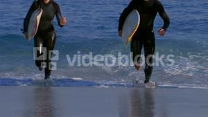 Three happy surfers running out of the sea