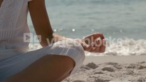 Part of a woman doing yoga on the beach