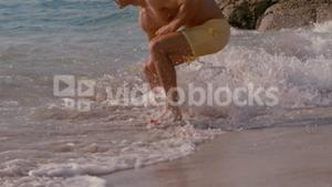 Athletic man running into the sea