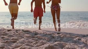 Happy friends running into the sea