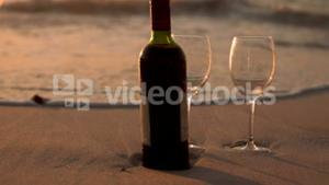 Red wine bottle and glasses on the beach sand