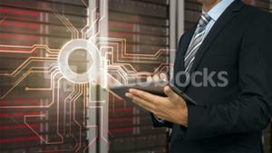 Businessman using tablet computer in front of locked server tower