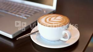 Cappuccino beside laptop on table