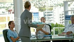 Businesswoman picking medical folder during medical meeting