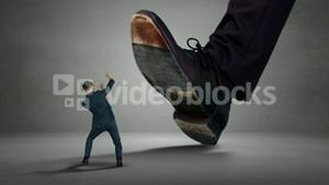 Shoes of boss trying to squash his employee