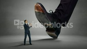 Shoes of giant boss trying to squash his employee