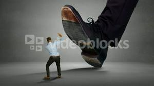 Shoes of giant boss trying to squash his scared employee