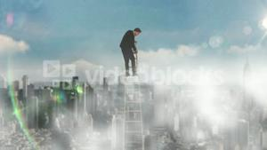 Businessman on ladder looking down on city background