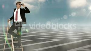 Businessman on ladder looking at labyrinth with binoculars