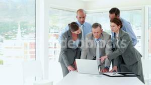 Business people looking at laptop computer during meeting