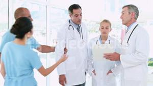 Doctors looking at clipboard and one of them going with surgeon