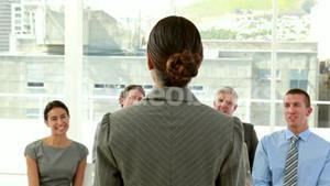 Happy business people looking at camera during presentation