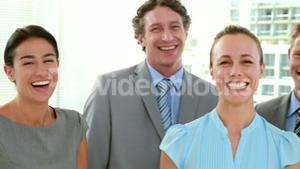 Happy business people looking at camera