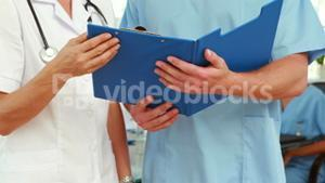 Two doctors holding clipboard in medical office