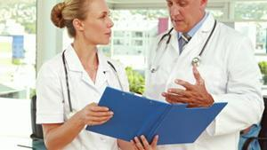 Two doctors looking at clipboard in medical office