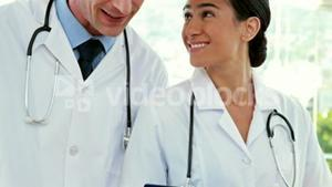 Happy doctors looking at clipboard