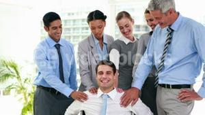 Business people smiling to their coworker on wheelchair