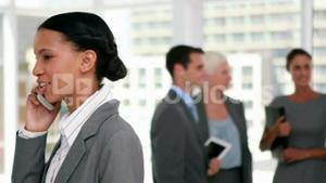 Businesswoman having a phone call with colleague in background