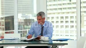 Serious businessman writing on notebook