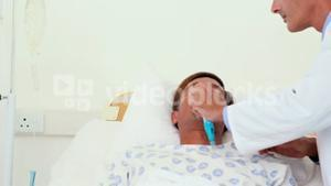 Doctor putting oxygen mask on patient head
