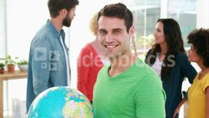 Casual businessman holding terrestrial globe with his colleagues behind